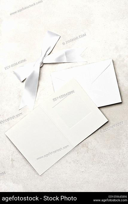 High angle shot of a group of a white envelope on a light gray desk top with white bow and blank cardboard picture frame