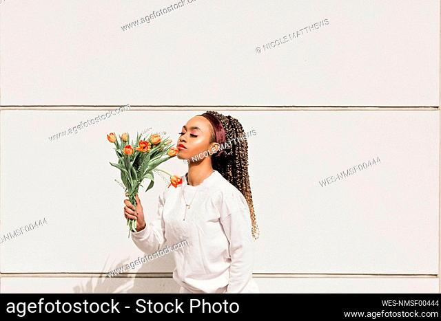 Young woman with eyes closed smelling flowers in front of white wall during sunny day