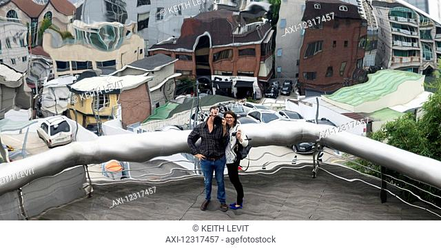 A couple distorted by window glass standing on a balcony with a view of buildings in the background below, Leeum samsung museum of art; Seoul, South Korea