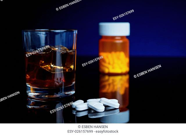 Alcohol and medicine. Glass, pills and bottle