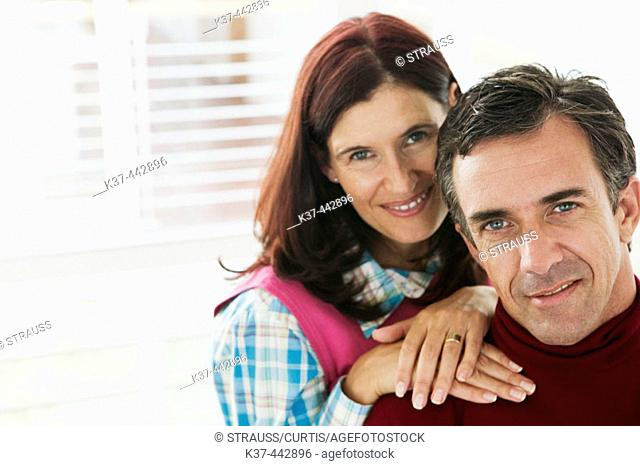 40-45 year old Caucasian couple relaxing in living room