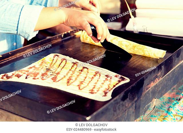 cooking, asian kitchen, sale and food concept - close up of cook frying pancakes at street market