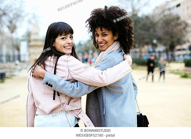 Spain, Barcelona, portrait of two happy women in city park embracing turning round