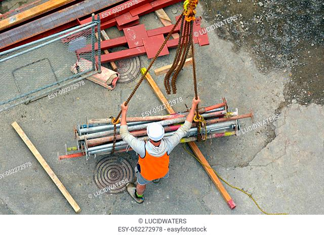 Aerial view of unrecognized worker builder manages the construction process of crane hook lifting work. Building development concept with copy space