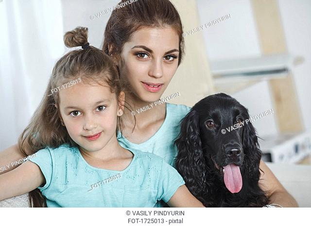 Portrait of beautiful young woman with daughter and dog at home