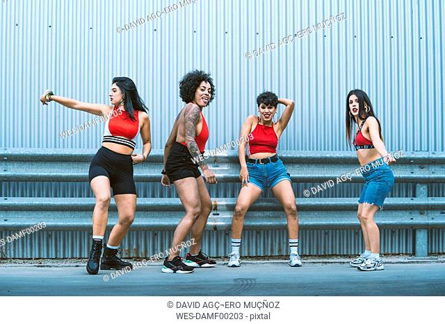 Four young sexy dancing on a strett in front of a wall
