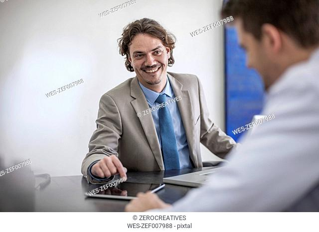 Smiling businessman at desk with laptop looking at man