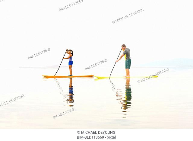 Couple riding paddle boards