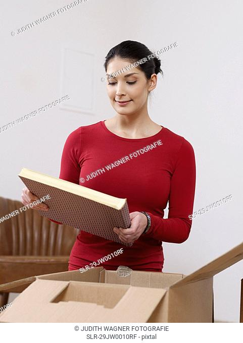 Young women unpacking books out of box