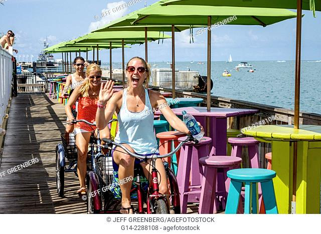 Florida, Key West, Sunset Key, Gulf of Mexico, Sunset Pier, restaurant, bar, pub, tables, umbrellas, colorful, woman, rental, bicycle, tricycle, friends