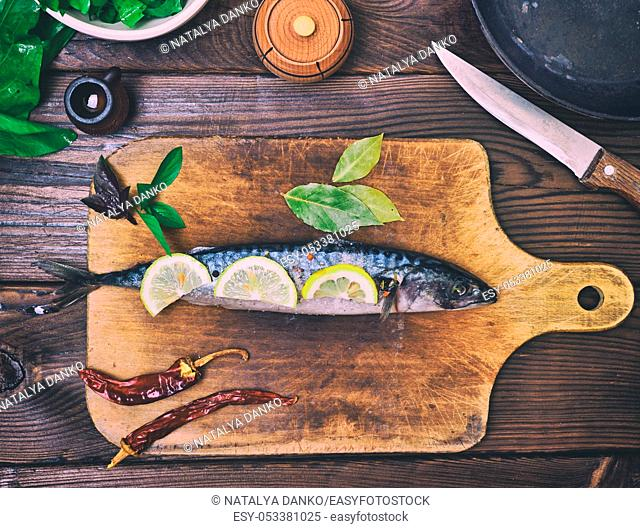 A fresh mackerel on a wooden kitchen board, top view
