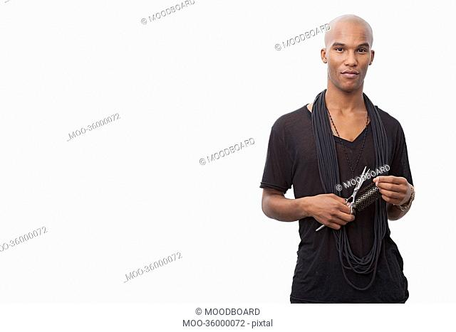 Portrait of young hairstylist standing against white background