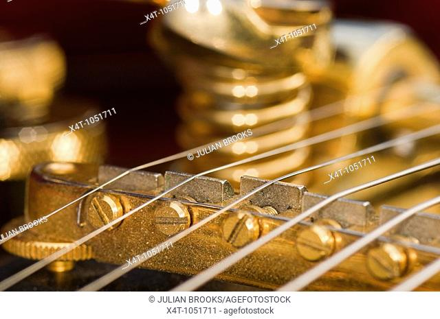 the strings on a Gretsch guitar, detail  showing how they are stretched over the bridge