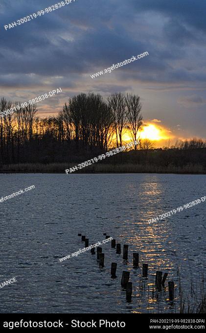 19 February 2020, Brandenburg, Falkenhagen: The sunset glows in a colourful way between dark rain clouds over the Gabelsee in the district of Märkisch-Oderland