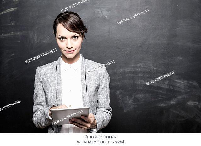 Portrait of a dark haired businesswoman using digital tablet