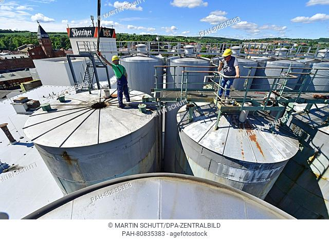 Two workers walking on top of the tanks at the dark beer brewery Koestritzer in Bad Koestritz, Germany, 31 May 2016. Two old tanks are removed and replaced with...