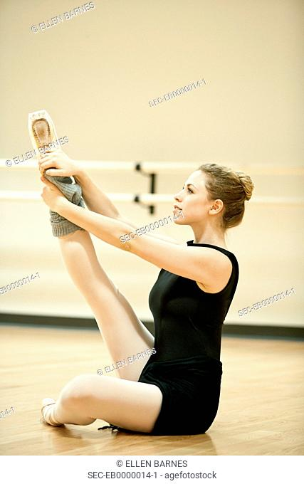 Ballet dancer stretching in daylight studio