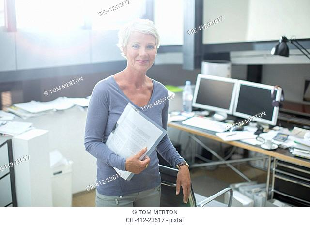 Businesswoman carrying paperwork in office