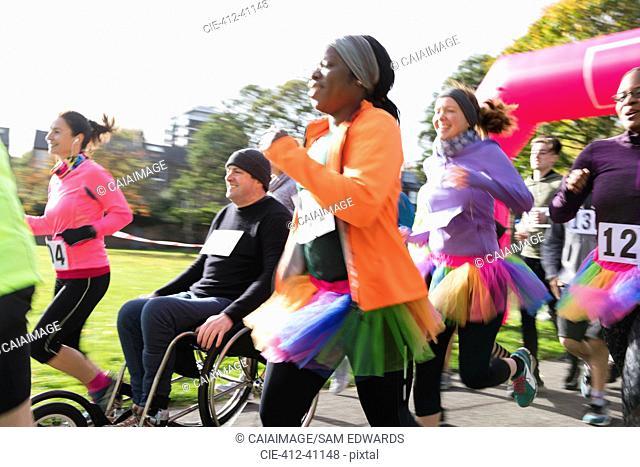 Female runner in tutu running in crowd at charity run in sunny park