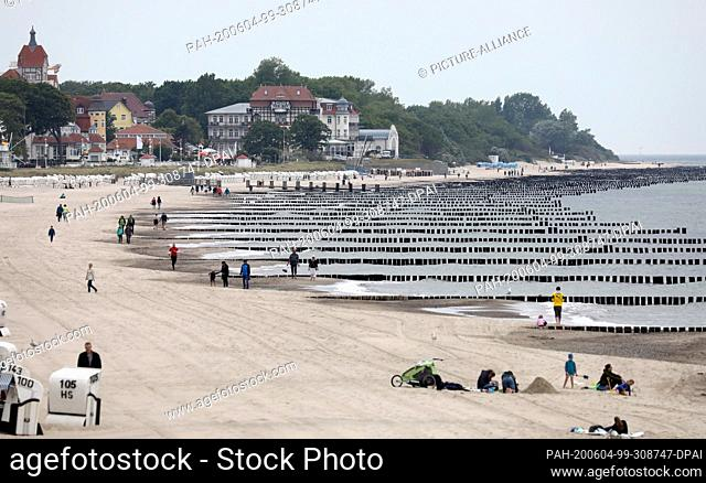 04 June 2020, Mecklenburg-Western Pomerania, Kühlungsborn: Some people walk across the beach. Thick clouds and sinking temperatures, however
