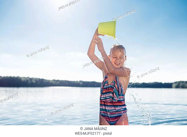 Portrait of smiling girl pouring water over her head
