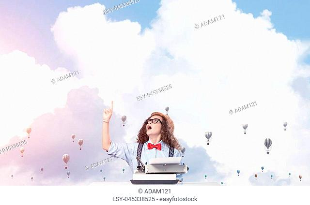 Young and beautiful woman writer in hat and eyeglasses using typing machine and pointing upside while sitting at the table with flying aerostats and cloudy...
