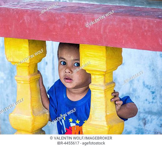 Little native boy looking through colourful balustrade, scared, Yangon, Myanmar