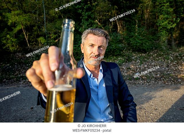 Portrait of mature businessman toasting with beer in nature