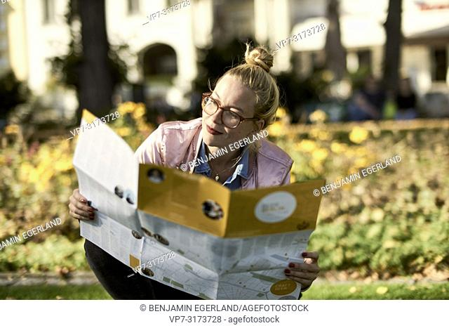 Woman with city guide map crouching on meadow in park, in Berlin, Germany