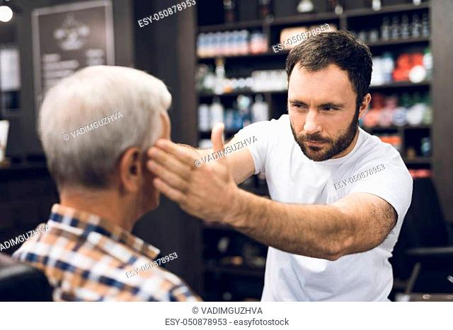 An old man with gray hair sits in a chair of a stylist in barbershop. Hairdresser preparing its cut, wears a cape