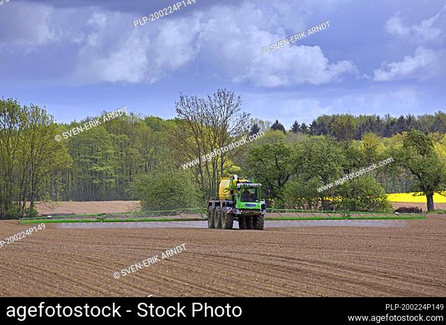 Farmer spraying pesticides / insecticides / weed killer / herbicide over field / farmland in spring