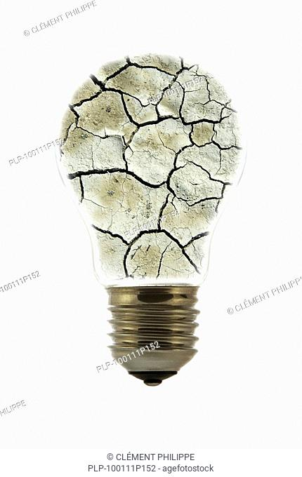 Cracked earth by drought inside incandescent lamp / bulb against white background