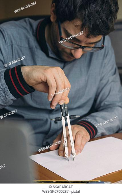Young man using compasses at desk