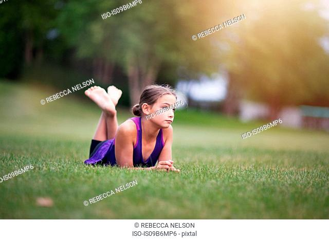 Girl lying on front on grass