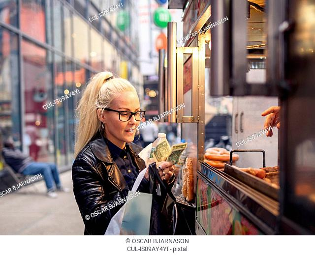 Female tourist buying hotdog at foodstall, New York, USA