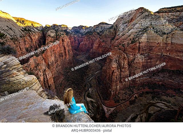 Woman sitting on edge of cliff and looking at view of canyon from Angels Landing, Zion National Park, Utah, USA