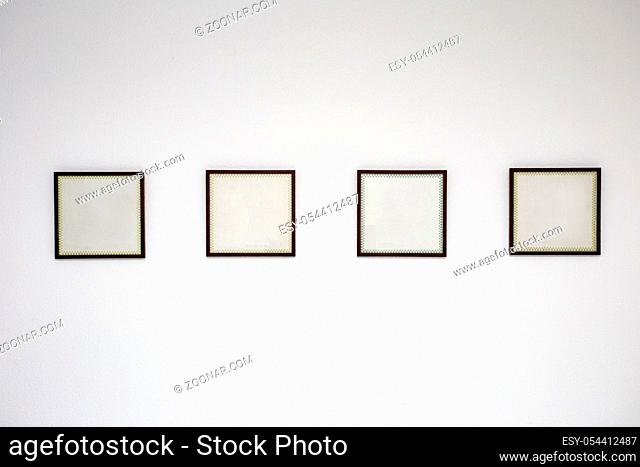 Blank black picture frame template for place image or text inside on the white wall in a row close-up