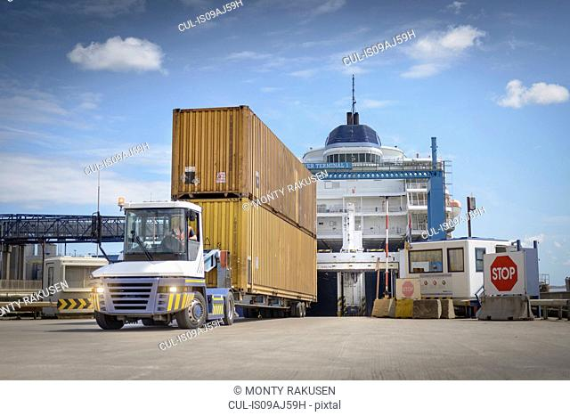Truck unloading shipping containers from ship to port