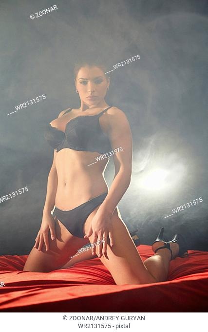 Dominant brunette with perfect body posing in bed
