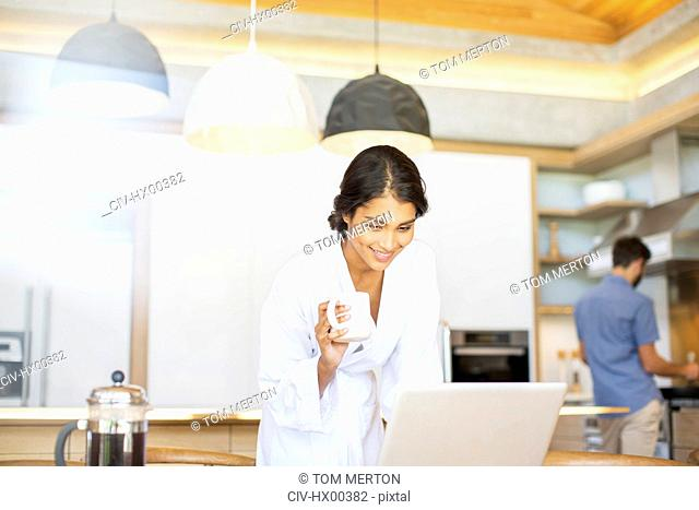 Woman in bathrobe drinking coffee and using laptop in kitchen