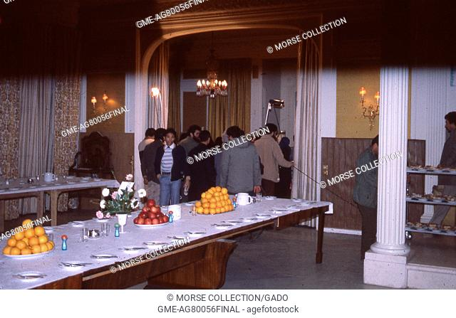 Scene of a long banquet table set with cutlery and large plates of fruits, in a hotel in Iran, March, 1983. In the background is a group of reporters and...