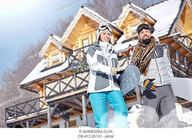 Snowboarder couple carrying snowboards below sunny cabin