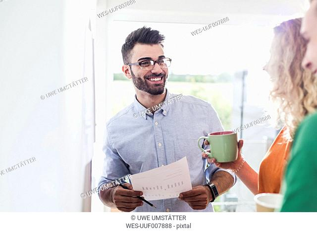 Smiling businessman with colleagues analysing data