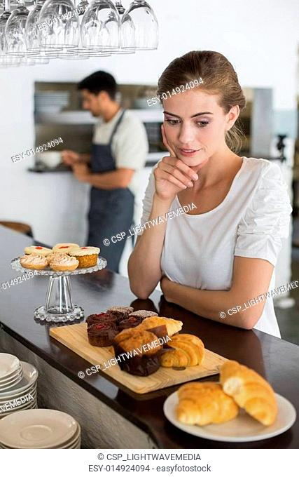 Cafe owner with sweet food at counter