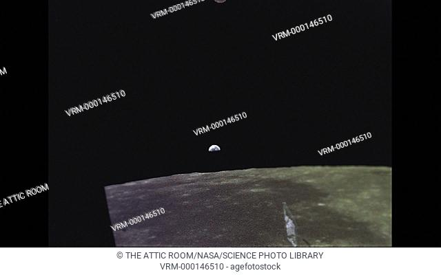 A small blue and white half illuminated view of the Earth rising into the black lunar sky from the Moon's horizon, as seen from the Lunar Module window