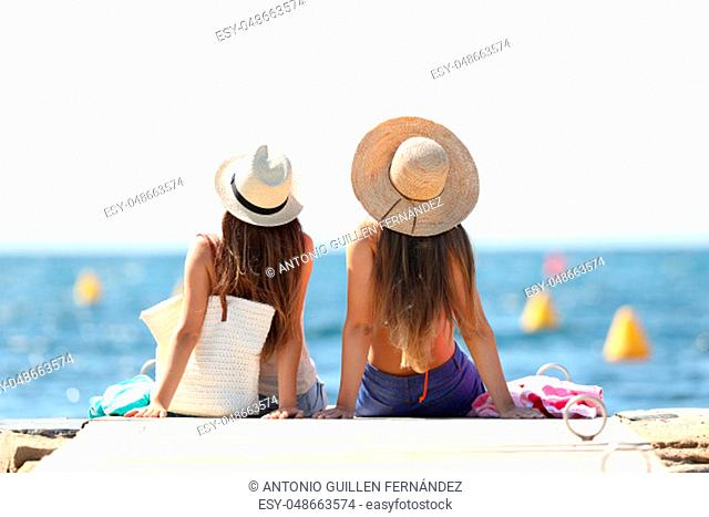 Back view of two tourists looking at horizon over the sea on summer vacations relaxing on the beach