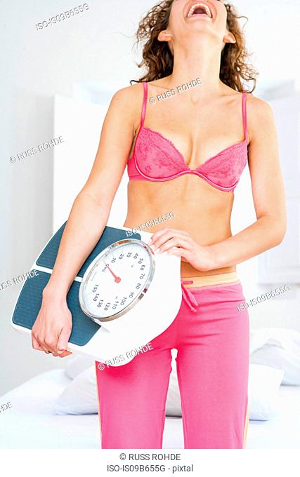 Woman holding bathroom scales head back laughing