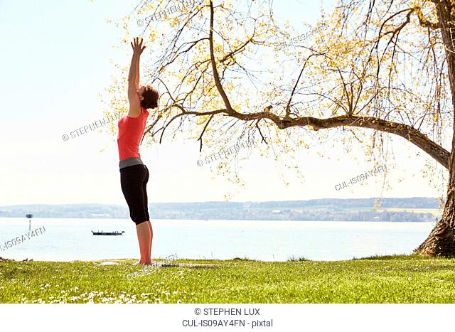Side view of woman, arms raised in yoga position