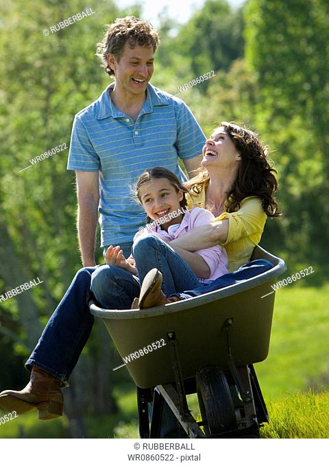 woman and her daughter sitting in a wheel barrow with a man standing beside them