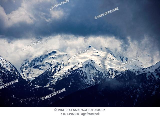 Snow storm moving in on the snow capped Olympic Mountains in the U.S
